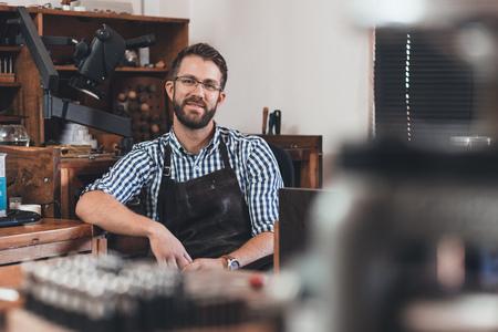 Portrait d'un jeune bijoutier souriant dans un tablier assis sur un banc complet d'outils dans son atelier