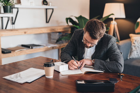 one man: Young entrepreneur sitting at a table at home looking focused while writing in notebook next to a small box