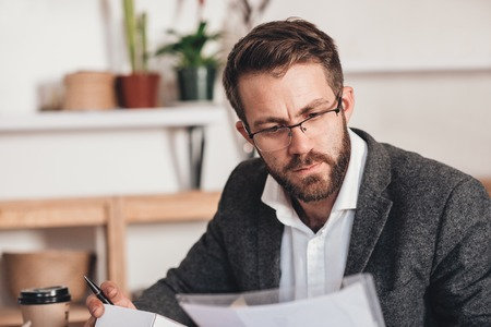 Young entrepreneur sitting at a table at home looking focused while reading paperwork and preparing small packages for delivery to customers