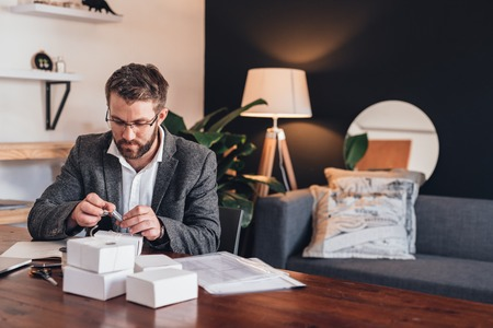 sitting at desk: Focused young entrepreneur sitting at a table at home heating up a stamp while preparing packages for delivery to customers