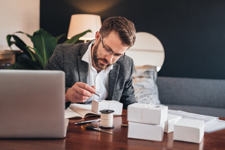package sending: Young entrepreneur sitting at a table at home looking focused while stamping a seal on a package for delivery to a customer Stock Photo