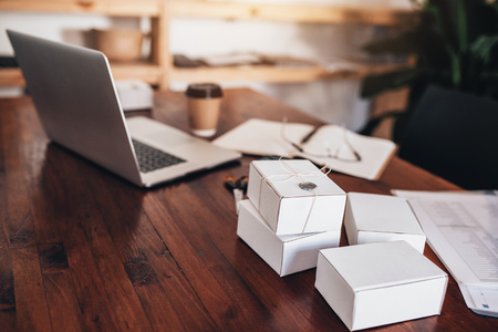small details: Closeup of a desk with a laptop, paperwork, scissors, string and boxes being prepared for shipping to customers Stock Photo