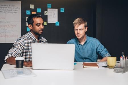 Deux designers qui collaborent ensemble sur un projet en face d'un ordinateur portable tout en travaillant dans un bureau
