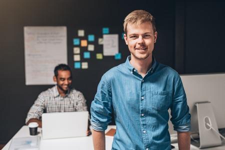 백그라운드에서 책상 랩톱 컴퓨터에서 작동하는 동료와 함께 사무실에 서 서 웃는 디자이너의 초상화