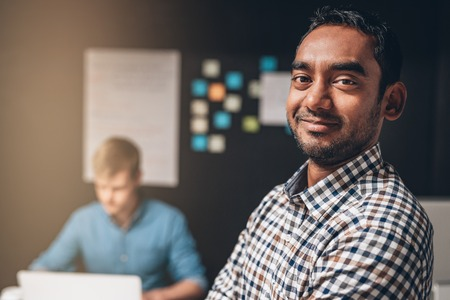 Portrait of a smiling designer standing in an office with a colleague working on a laptop computer at a desk in the background Standard-Bild