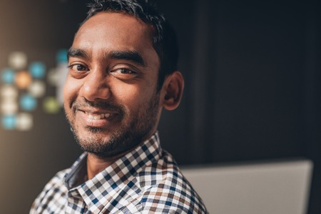 open collar: Closeup portrait of a smiling entrepreneur standing in an office with a computer in the background