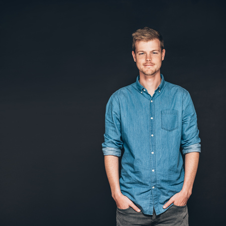 go inside: Studio portrait of a smiling and confident young entrepreneur standing with his hands in his pockets in front of a dark background Stock Photo