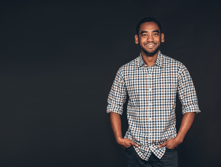 open collar: Studio portrait of a smiling and confident young entrepreneur standing with his hands in his pockets in front of a dark background Stock Photo