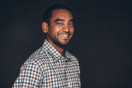 open collar: Studio portrait of a confident young entrepreneur standing crossed in front of a dark background Stock Photo