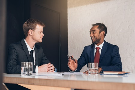 Two young businessmen in suits discussing documents together while sitting at a table in a modern boardroom Stock Photo