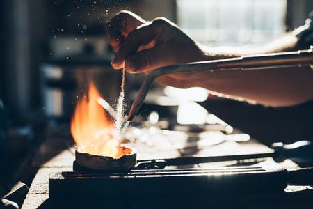 Nahaufnahme eines Juwelier eine Taschenlampe unter Verwendung von Metall in einem Tiegel zu schmelzen, während in seinem Schmuck-Design-Studio zu arbeiten