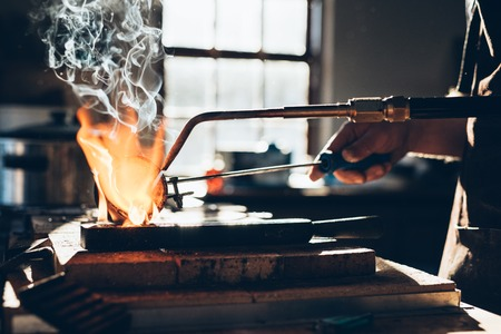 crucible: Closeup of a jeweler using a torch to melt metal in a crucible while working in his jewelry design studio