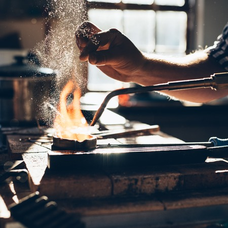 Closeup of a jeweler using a torch to melt metal in a crucible while working in his jewelry design studio