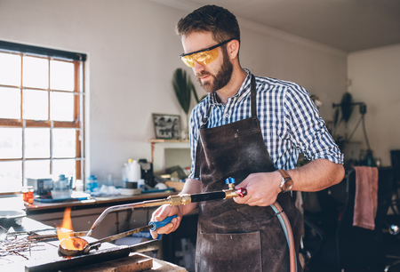 crucible: Focused jeweler using  a torch to melt metal in a crucible while working in his jewelry design studio Stock Photo