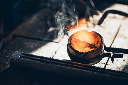 crucible: Closeup of a jeweler using  a torch to melt a metal ingot in a crucible while working in his jewelry design studio Stock Photo
