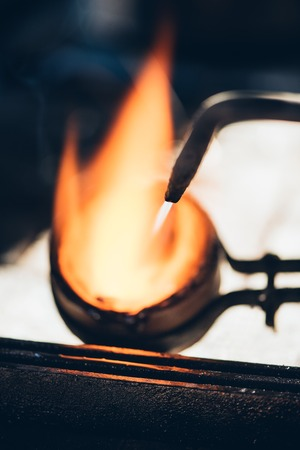 jewelry design: Closeup of a jeweler using a torch to melt metal in a crucible while working in his jewelry design studio
