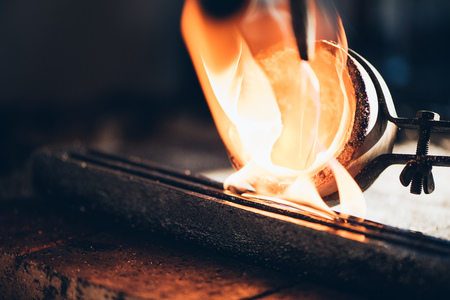 jewelry design: Closeup of a jeweler pouring molten metal from a crucible into a mold while working in his jewelry design studio Stock Photo