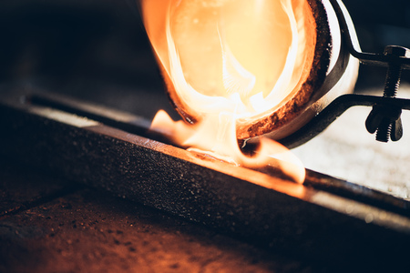 crucible: Closeup of a jeweler pouring molten metal from a crucible into a mold while working in his jewelry design studio Stock Photo