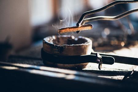 Primer plano de un joyero se utiliza un soplete para fundir un lingote de metal en un crisol mientras se trabaja en su estudio de diseño de joyería