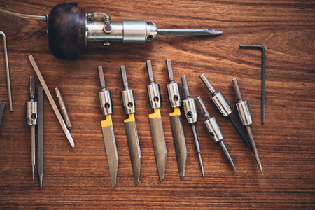 engraver: Closeup of a collection of hand engraving tools sitting on a table in a jewelery workshop