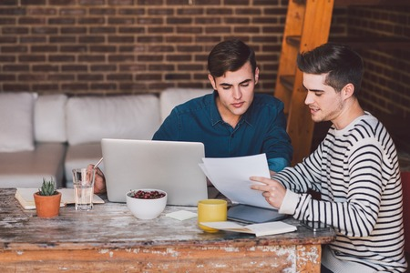home business: Young business owners sitting at a table at home discussing paperwork over a laptop while working together on their home based business