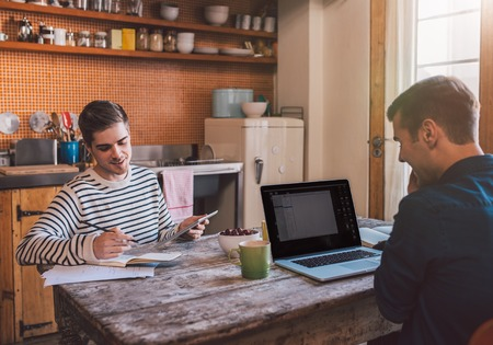 business media: Young gay couple sitting at the kitchen table at home using a laptop and digital tablet while working together on their home based business Stock Photo