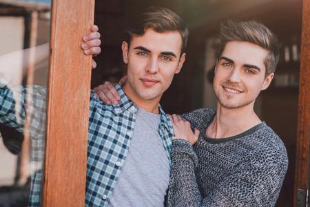 自分のアパートへの扉で welcomingly 笑顔の若い同性愛者のカップルの立っている肖像画 写真素材 - 65787782