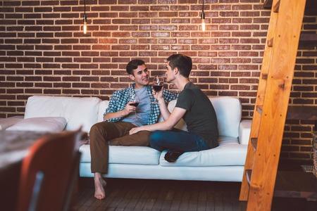 tomando vino: Cariñosa pareja alegre joven sentado en su casa junto a su sofá de la sala de hablar y beber vino tinto
