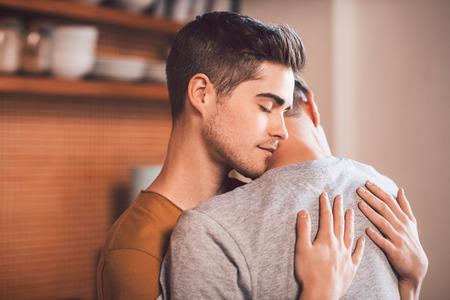 아침에 자신의 부엌에 서있는 동안 자신의 눈으로 서로 포옹 애정 어린 게이 커플 폐쇄 스톡 콘텐츠