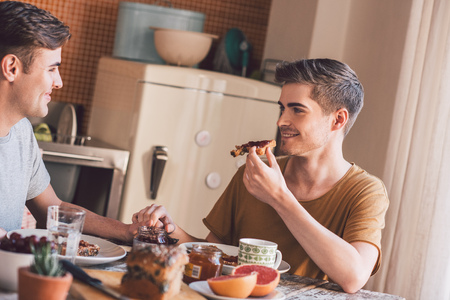 homosexual partners: Smiling young gay couple talking and eating breakfast together while sitting at their kitchen table in the morning Stock Photo