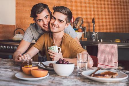 Portrait d'un jeune couple gay affectueux qui mange le petit-déjeuner ensemble assis à la table de la cuisine le matin