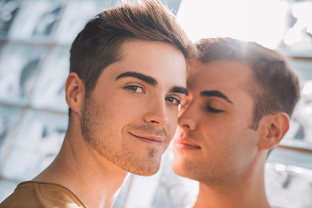 自宅近くに立っている愛情のこもった若い同性愛者カップルの肖像画 写真素材 - 65787962