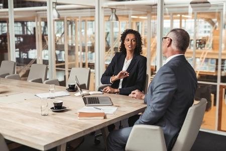 사무실 회의실에서 테이블에 앉아있는 동안 사업을 논의 성숙한 사업가 및 젊은 직장 동료