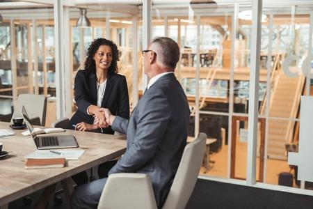 Ltere Geschäftsmann und junge Arbeit Kollegen Händeschütteln beim Sitzen zusammen an einem Tisch in einem Büro Sitzungssaal Standard-Bild - 65788009