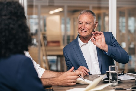 Mature businessman talking with young staff members while sitting together at a table in an office boardroom Stock Photo