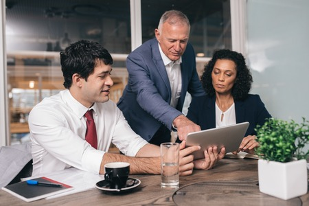 diverse: Three diverse businesspeople talking together over a digital tablet while working at a table in an office boardroom