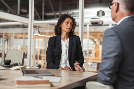 homme d'affaires d'âge mûr et jeune collègue de travail discuter des affaires tout en étant assis ensemble à une table dans une salle de réunion de bureau Banque d'images