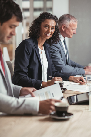 ethnicity: Portrait of a smiling young businesswoman sitting at a boardroom table with a diverse group of colleagues