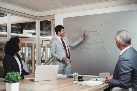 strategy meeting: Young businessman standing in a boardroom giving a presentation on a whiteboard to two work colleagues sitting a table