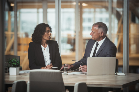 Mature businessman and young work colleague discussing business while sitting together at a table inside a glass office boardroom