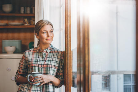 looking through window: Attractive young blonde woman drinking a cup of coffee and thinking while looking out the window of her apartment Stock Photo