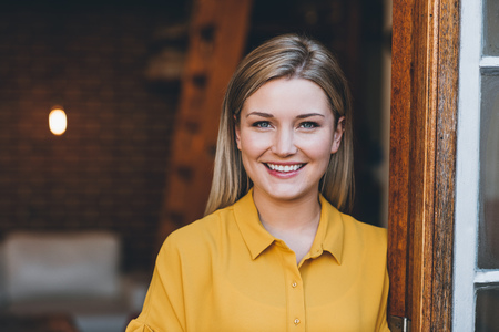Portrait of an attractive young blonde woman smiling while standing at the door to her modern loft apartment Zdjęcie Seryjne - 65788549
