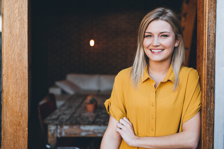 Portrait of an attractive young blonde woman smiling while standing at the door to her modern loft apartment