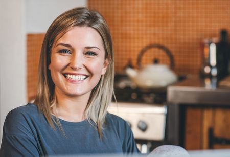 Portrait of an attractive young blonde woman smiling while sitting in her kitchen in the morning