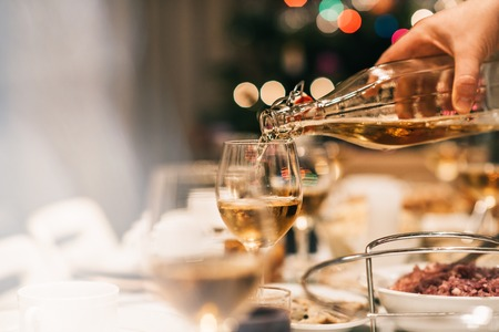 Closeup of a man pouring white wine into a glass on a dining table full of food with a Christmas tree in the background