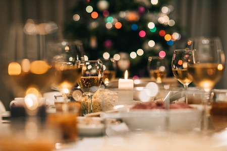 Dining table full of a variety of delicious festive food and wine with a Christmas tree in the background Stock Photo