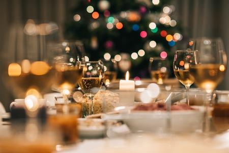 Mesa de comedor llena de una variedad de deliciosa comida festiva y el vino con un árbol de Navidad en el fondo Foto de archivo