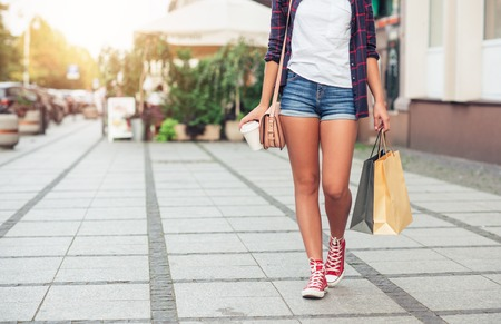 waist down: Young woman walking and shopping in the city