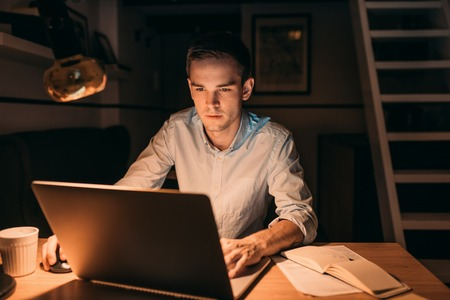 working late: Young businessman working on a laptop late in the evening Stock Photo