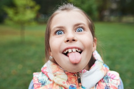 grinning: Cute little girl sticking out her tongue Stock Photo